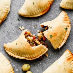 Baked empanadas with the one in the center torn in half.