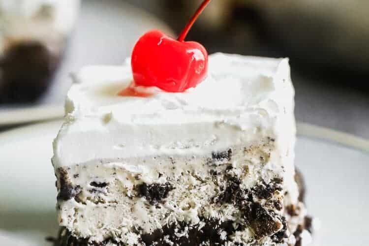 A slice of ice cream cake with a cherry on top, served on a plate.