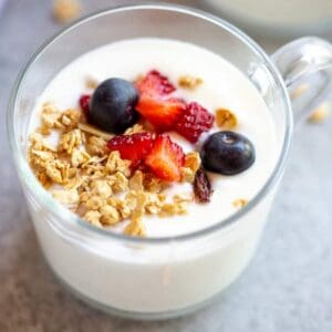 Instant pot yogurt served in a cup with berries and granola on top.