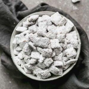 A bowl of muddy buddies (puppy chow) on a grey towel.