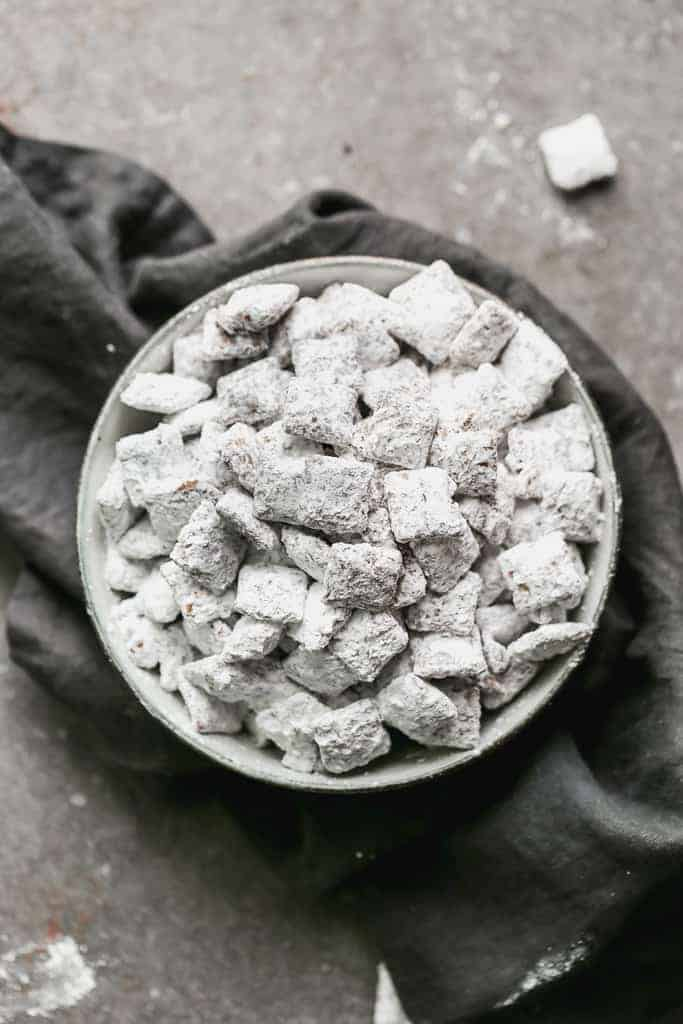 A bowl of muddy buddies (puppy chow) on a grey hand towel.