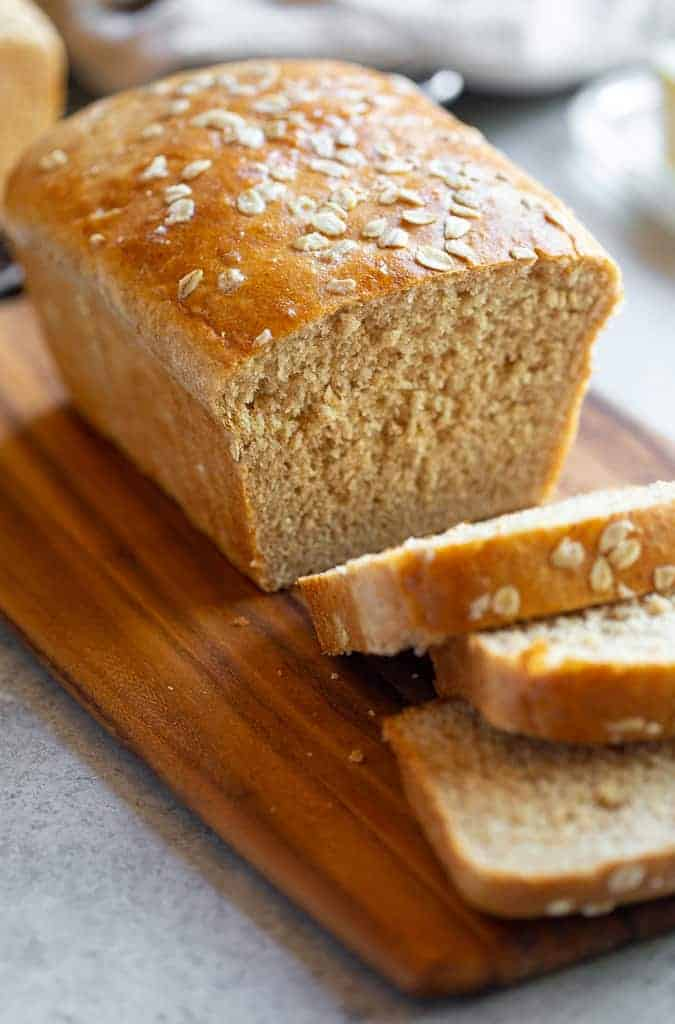 Freshly baked oatmeal bread on a cutting board.