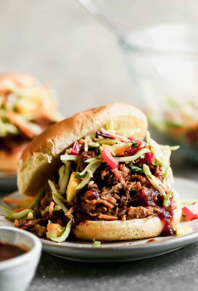 A BBQ pulled pork sandwich with slaw, in a bun, served on a plate.
