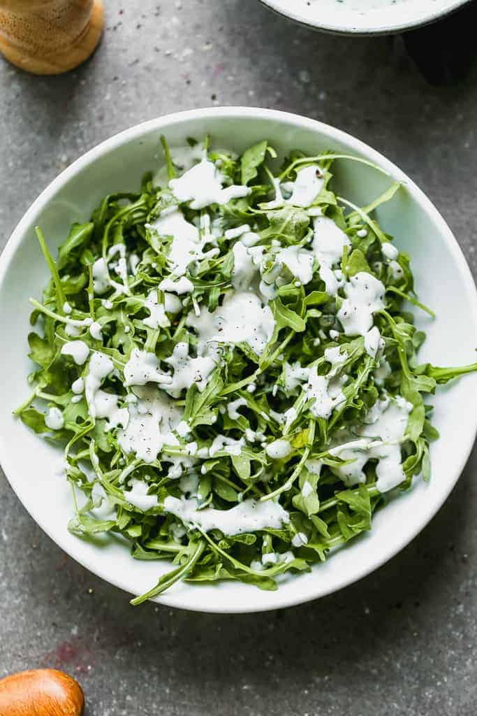 A green salad with homemade ranch drizzled on top.