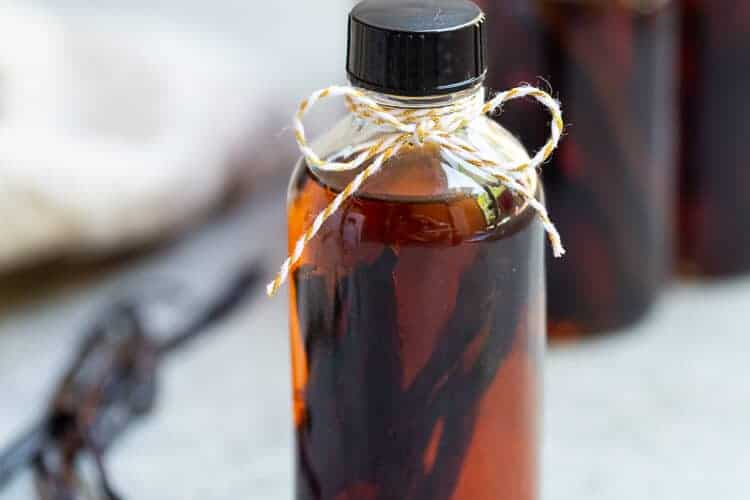 A small bottle of homemade vanilla extract with vanilla beans and vodka inside.