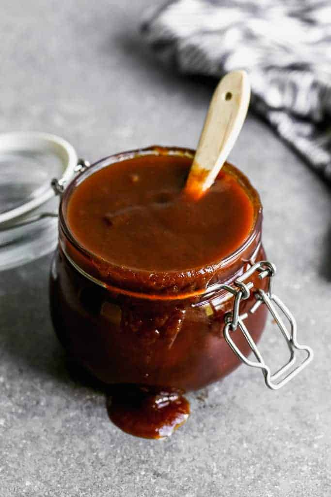 BBQ sauce in a glass jar with a basting brush in it.