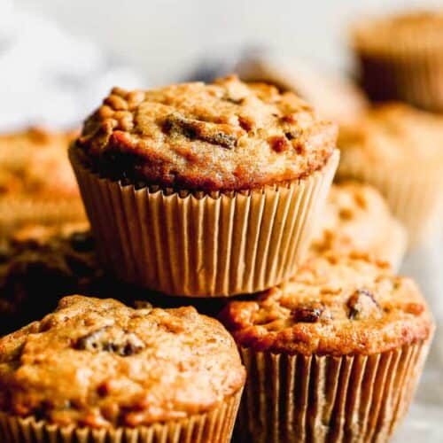 Bran muffins baked in muffin liners, stacked on a board.