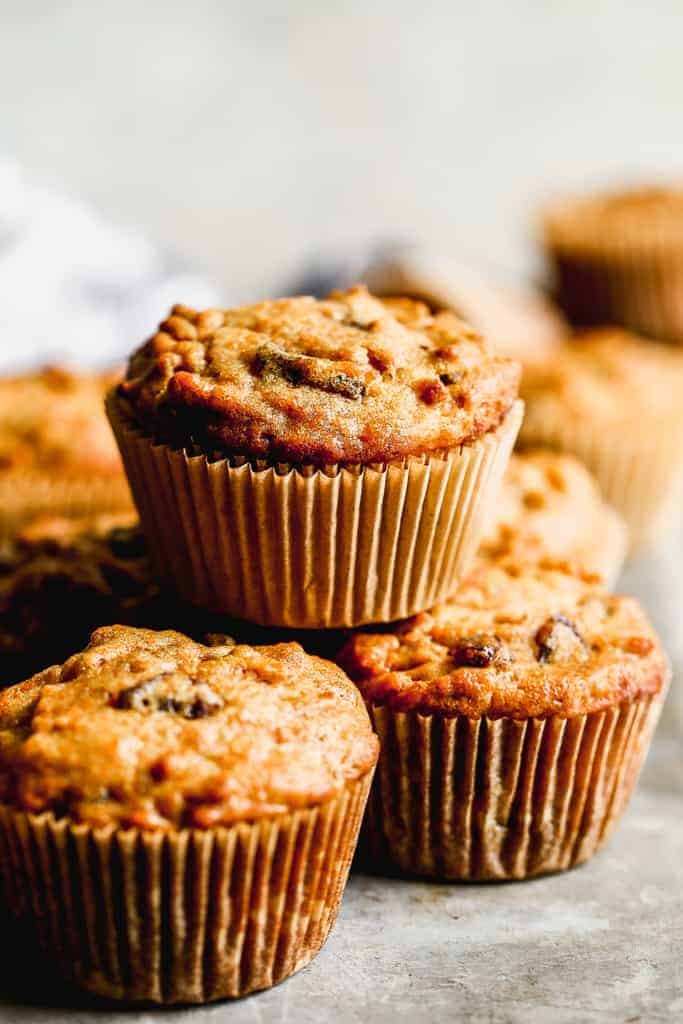 A stack of freshly baked Bran Muffins baked in paper muffin liners.