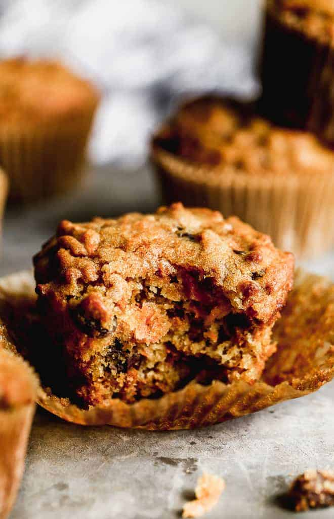 A bran muffin with a bite taken out of it.