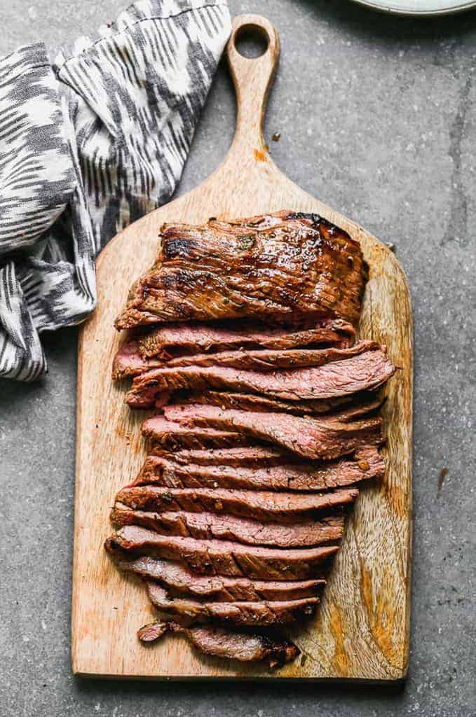 Grilled, sliced carne asada steak, served a on wooden board.