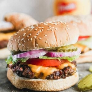 A hamburger in a sesame bun with cheese, tomato, lettuce, onion and pickle.