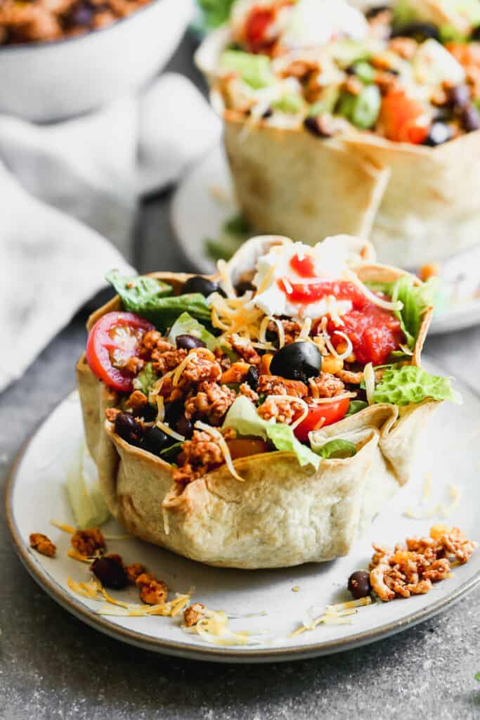 Taco salad served in a baked tortilla bowl, on a plate.