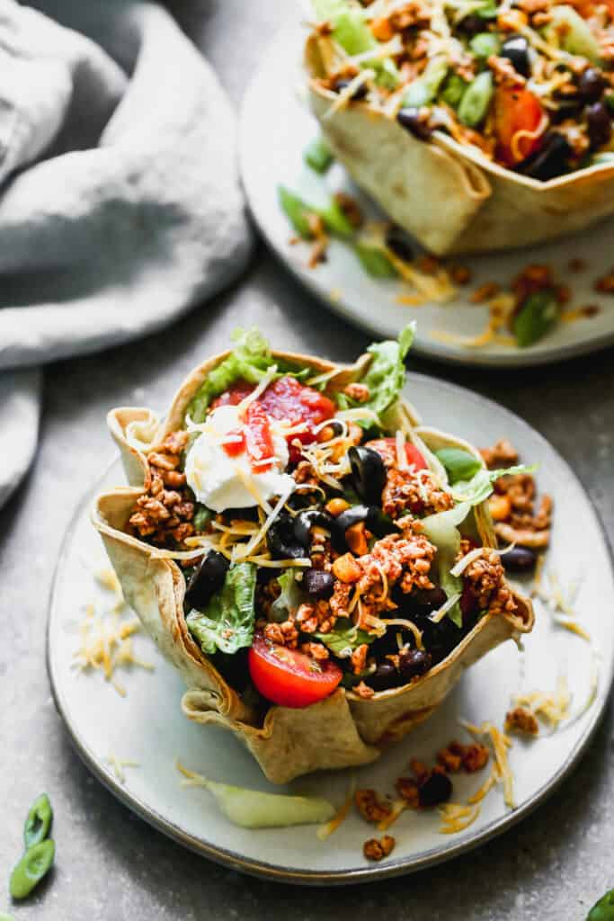 A taco salad made with ground beef, black beans, corn, lettuce, tomato, olives, in a flour tortilla shell.