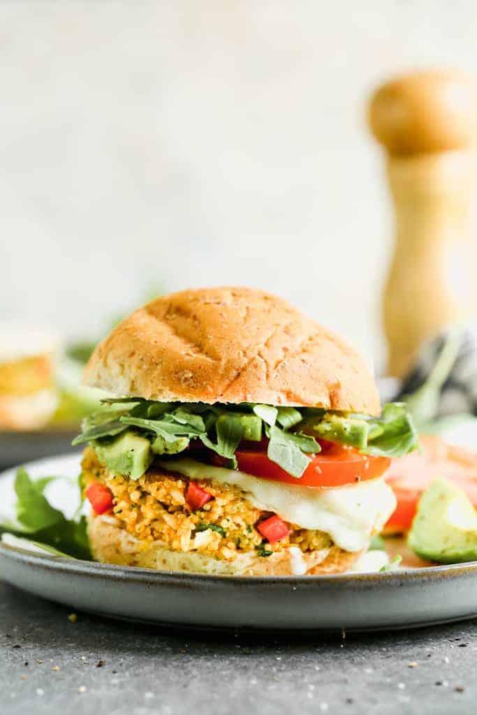 Burger végétarien servi sur un petit pain de blé dans une assiette.