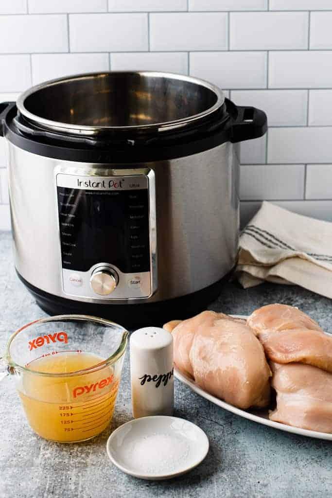 Les ingrédients nécessaires pour les poitrines de poulet instantanées, y compris le poulet cru, le sel et le poivre et le bouillon de poulet.