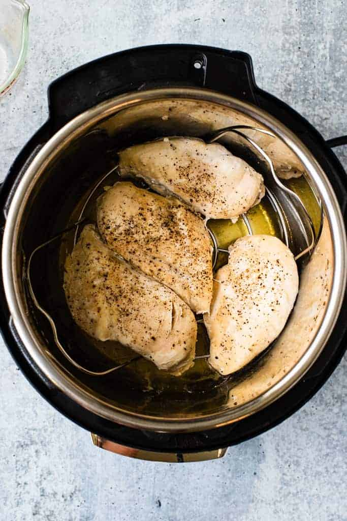 Four cooked chicken breasts resting in the bottom of an instant pot.