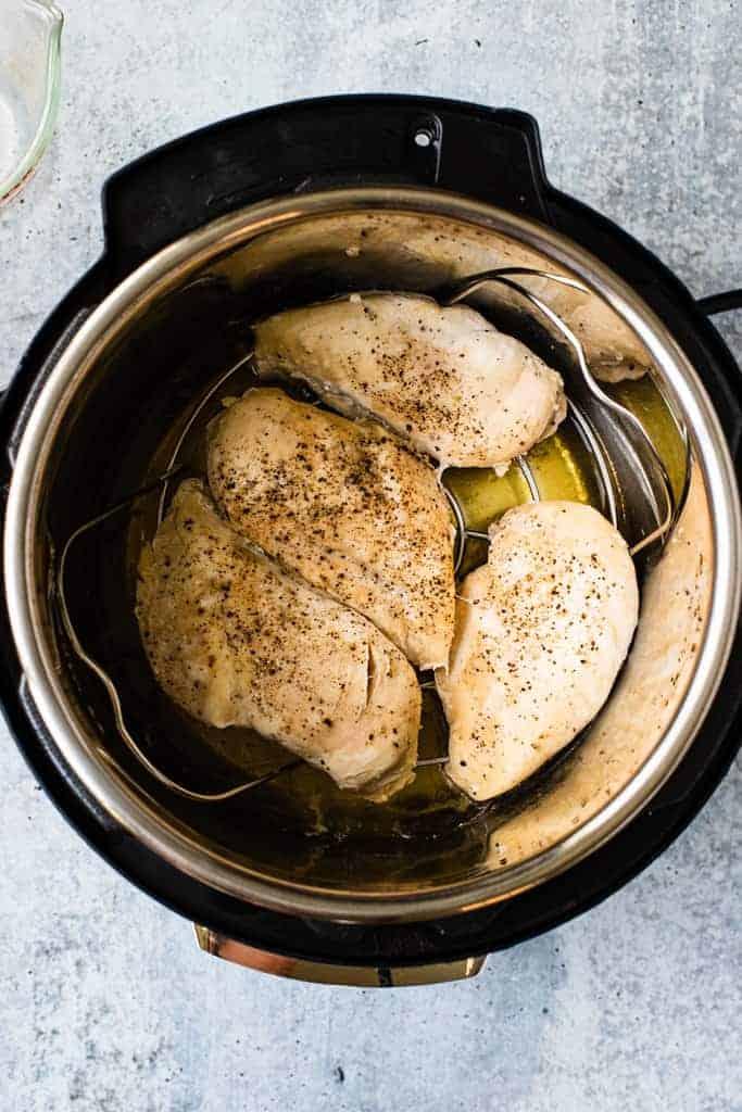 Quatre poitrines de poulet cuites reposant au fond d'une casserole instantanée.