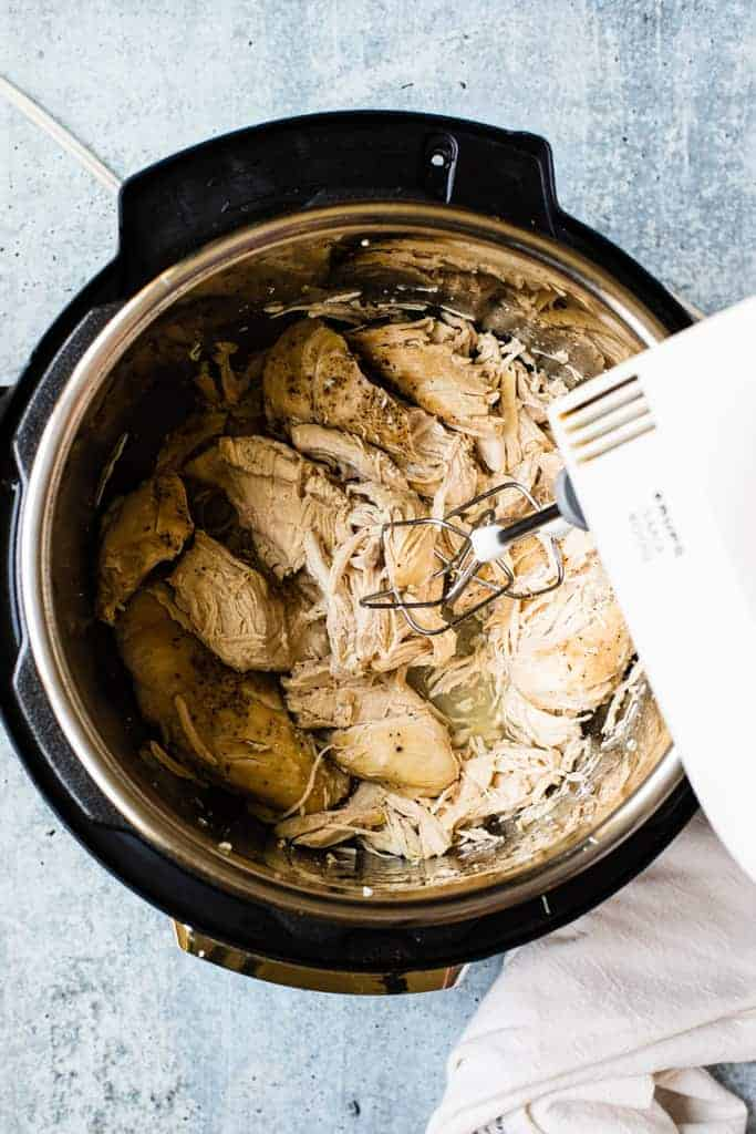 Mixers shredding cooked chicken inside an instant pot.