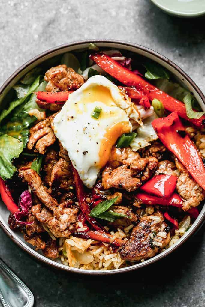 Korean Bulgogi Bowl with a mix of meat, veggies and greens, rice, and an egg on top.