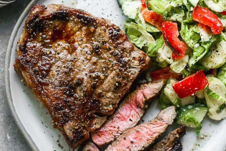 A medium rare grilled steak on a plate with a few slices cut from it and a green salad on the side.