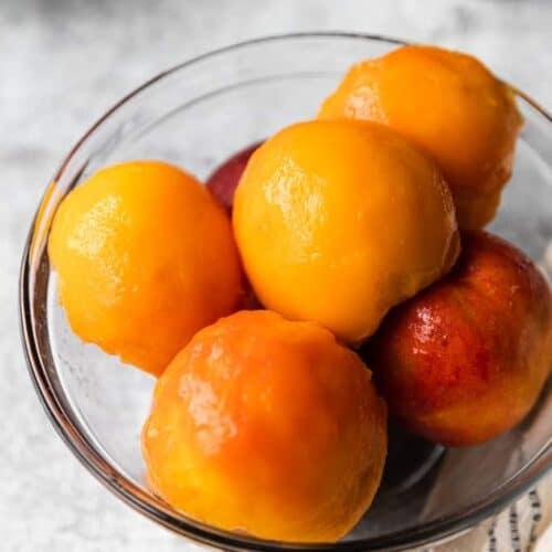 A bowl of peeled, fresh peaches.