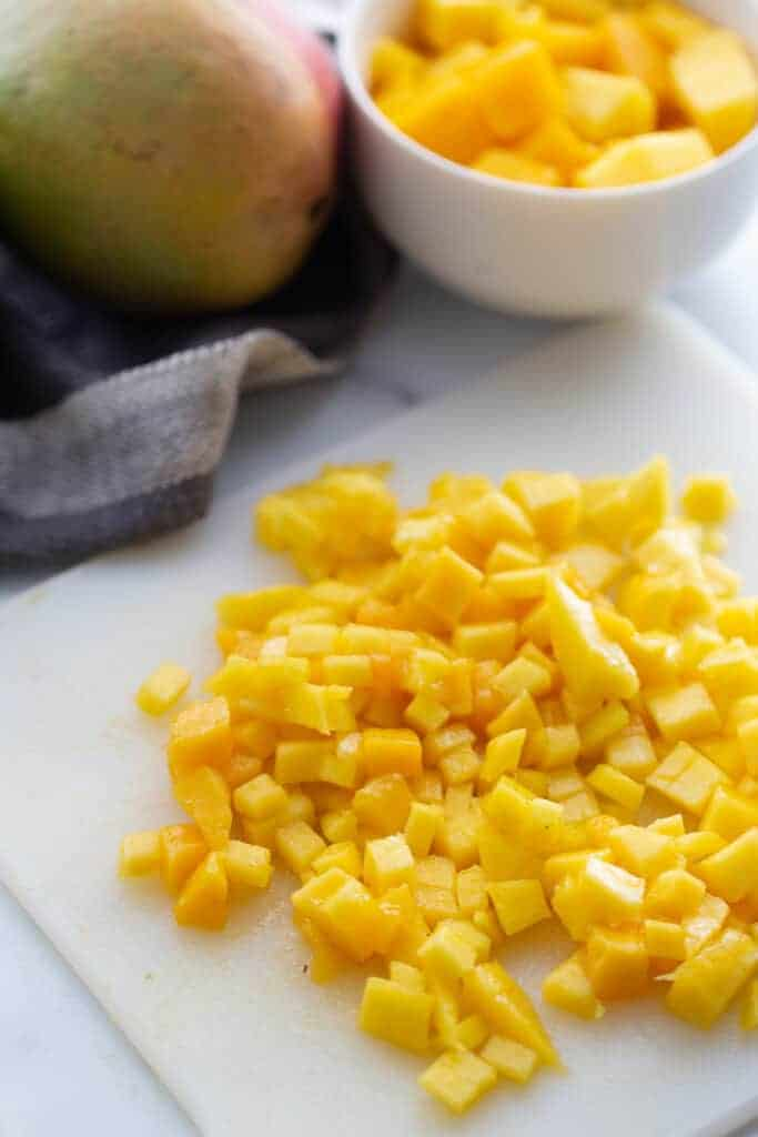 Diced pieces of mango on a cutting board.