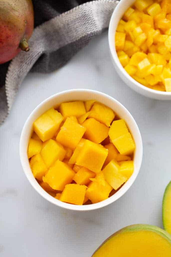 A bowl with cut cubes of mango in it.