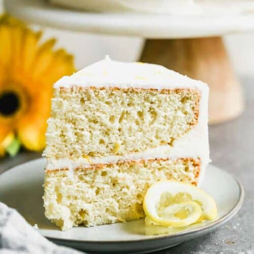 A slice of Lemon Cake standing up on a plate.
