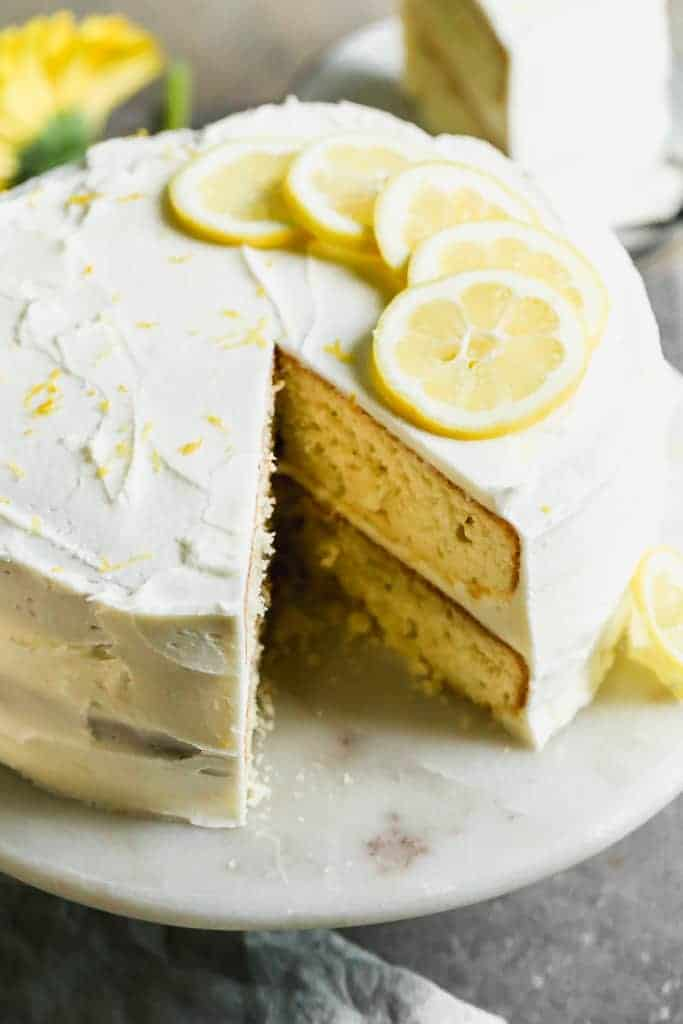 A two-tier round Lemon Cake frosted with lemon buttercream frosting and fresh lemon slices placed on top.
