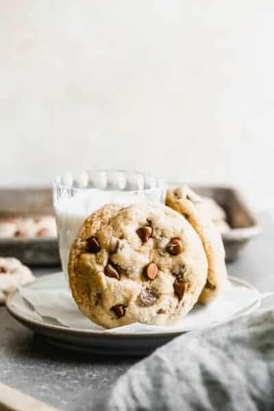 Oatmeal chocolate chip cookies propped up a on plate with a glass of milk.