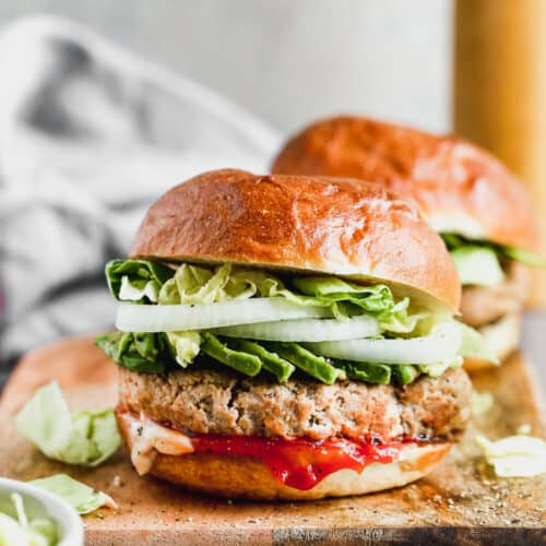 Two turkey burgers served in buns, topped with avocado, lettuce and onion.