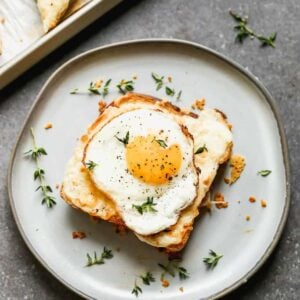 A Croque Madame sandwich served on a plate (with a cooked egg on top).
