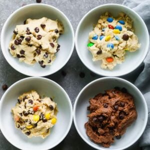 Four bowls with different flavors of edible cookie dough in them including chocolate chip, peanut butter, chocolate, and M&M cookie dough.