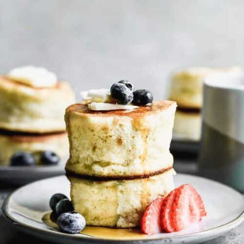 Two Japanese souffle pancakes stacked on each other, on a plate with fresh berries.