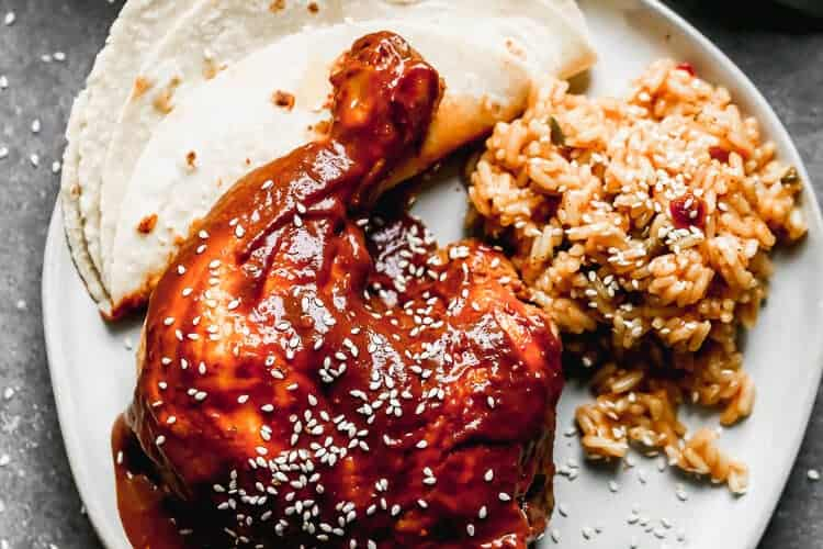 A plate with mole sauce served over chicken with a side of Mexican rice and a tortilla.