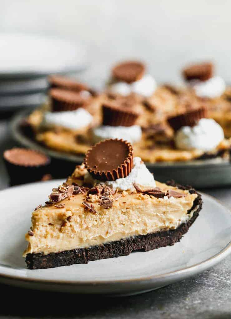 A slice of peanut butter pie on a plate, topped with whipped cream and a Reese's peanut butter cup.