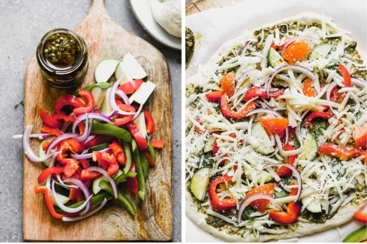 A cutting board with chopped veggies and pesto sauce in a jar, next to a veggie pizza, ready to go in the oven.