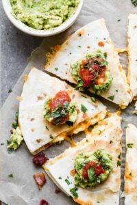 Breakfast quesadilla cut into triangles, topped with sour cream, salsa and guacamole.