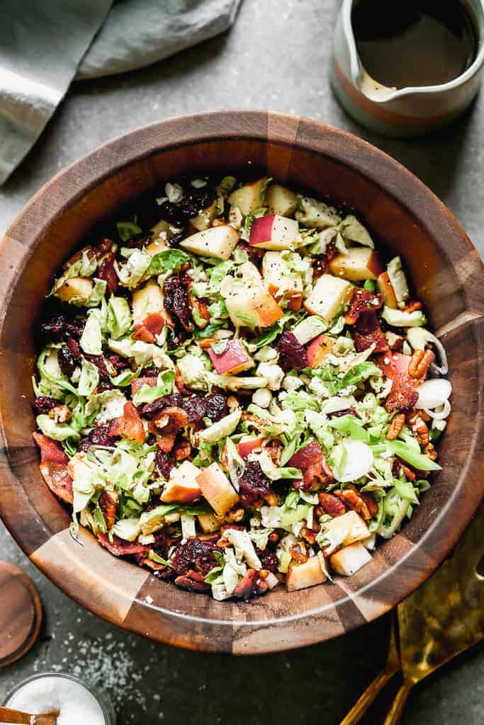 Brussels sprout salad with apples and bacon, served in a wooden serving bowl.