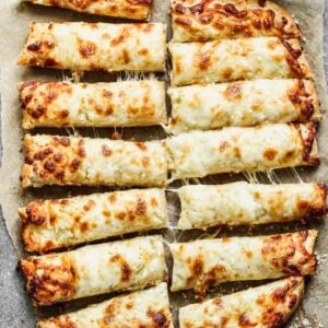 Cheesy breadsticks cut into pieces, with marinara sauce in a bowl on the side.