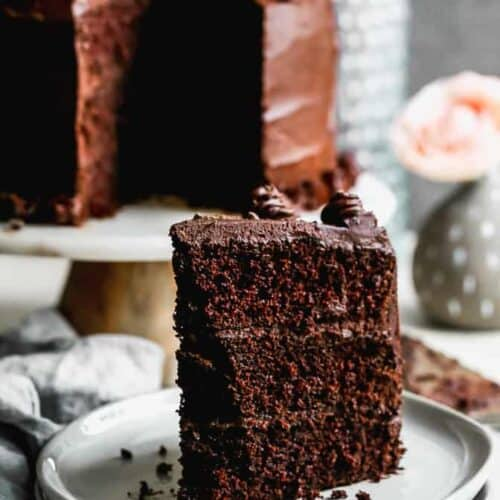 A slice of dark chocolate cake on a white plate and the remaining cake in the background.