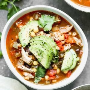 A bowl of fajita soup with chicken, corn and black beans, garnished with fresh avocado and cilantro.