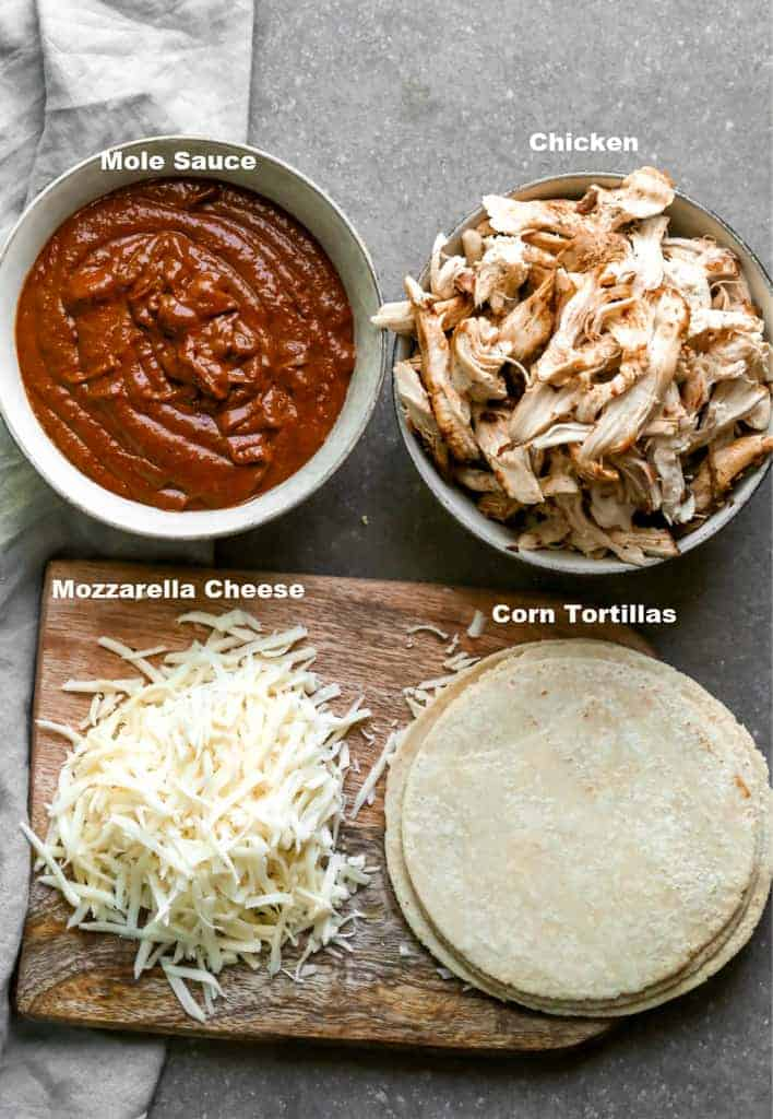 The ingredients needed to make mole enchiladas including mole sauce, chicken, cheese and tortillas.