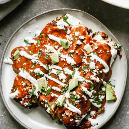 Three mole enchiladas on a plate, garnished with sour cream, cotija cheese, cilantro and avocado.