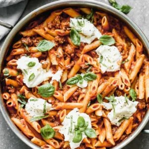 A large pan of cooked Skillet Lasagna, topped with spoonfuls of ricotta and fresh basil.