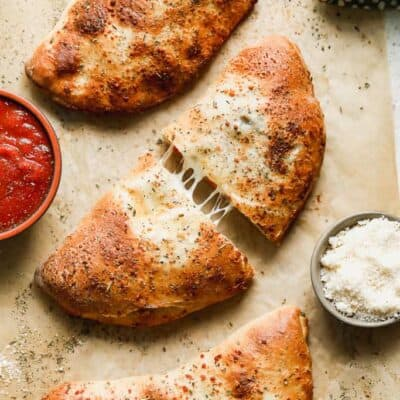 Three calzones on parchment paper with a side of marinara sauce.