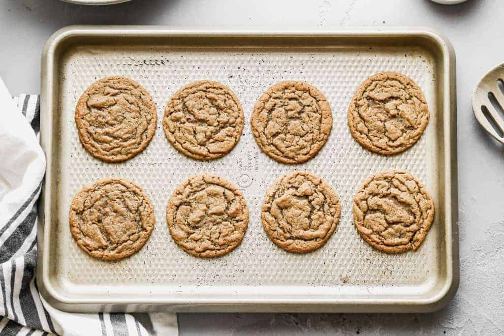 A cookie sheet with baked gingersnap cookies on it.