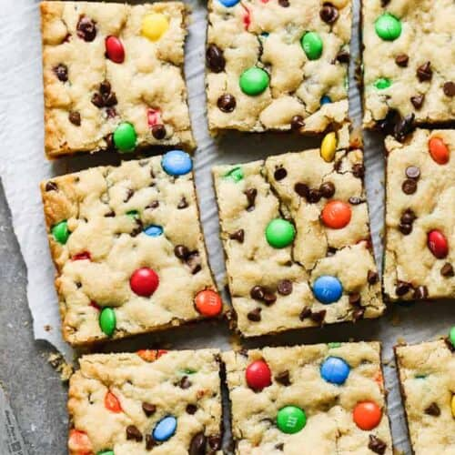 M&M Cookie Bars cut into squares on a board with parchment paper.