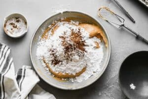 A bowl with pumpkin pie mix, beaten cream cheese, powdered sugar and spices added to make pumpkin dip.