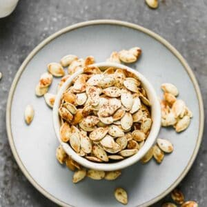 A bowl of roasted pumpkin seeds sitting on a plate, with some seeds spilling over onto the plate.